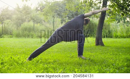 A man doing yoga exercises in the park. Utthita trikonasana
