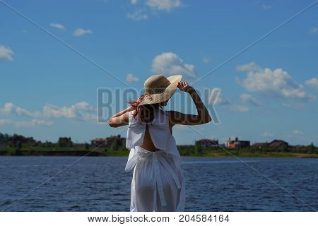 Woman In White Dress And Glamour Hat On Riverside