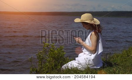 Beautiful Red-haired Girl In A White Summer Dress Uses A Cell Phone Sitting On The Shore And Rivers