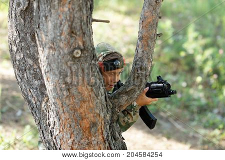 Child In Camouflage With A Gun Shoots, Laser Tag