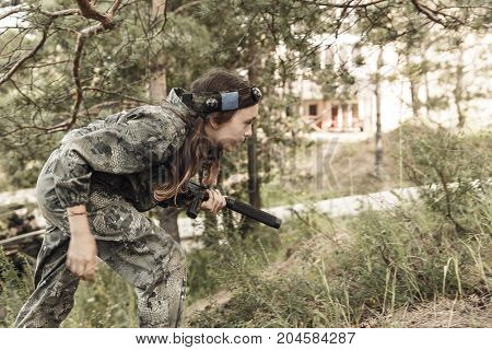 Young boy with a gun laser tag war simulation. Lasertag shooting game. Military sport