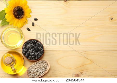 Sunflower Oil, Seeds And Flower On Light Wooden Background. Top View With Copy Space