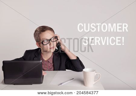 Cute little boy in a suit talking on the phone next to inscription 'Customer service'