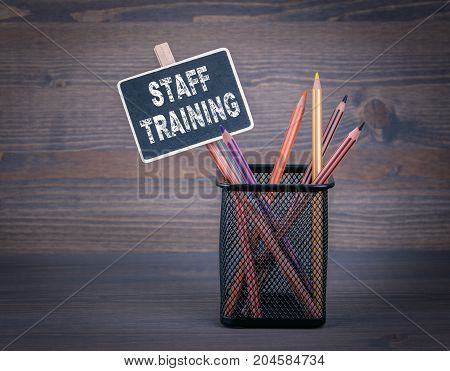 Staff Training concept. A small blackboard chalk and colored pencil on wood background.