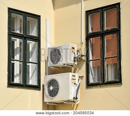 Air conditioners between two window on the wall