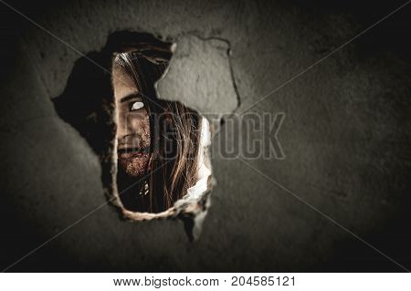 Zombie woman staring into a hole on the wall horribly. Women dressed in costume cosplay zombies on Halloween.