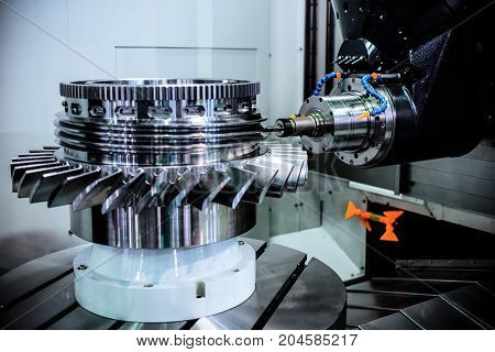A modern CNC milling machine makes a turbine wheel. Accurate metal working. Shooting in real conditions, maybe some blurring and grain.