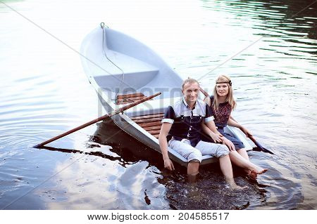 sweet tenager sitting on the edge of boat, beautiful guy and girl having fun in a boat outdoors, nice couple have fun in a boat on the lake