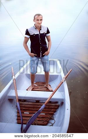 young man standing in the white boat, handsome teenager in light shorts and shirt, guy enjoys outdoor recreation