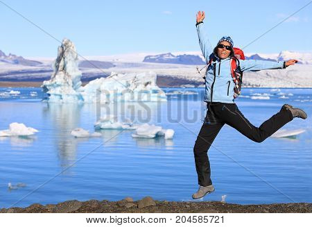 Girl in waterproof clothing has fun jumping on the coast of the large glacial lake Jokulsarlon in southeast Iceland