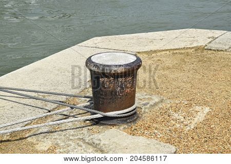 Bollard next to the river with wire cable