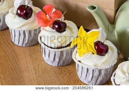 delicious cherry cakes with flowers for decorating cream