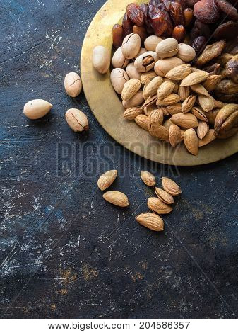 Various nuts and dried fruits on a copper plate on a dark background. Dates, figs, almonds, pecans. Top view. Copy space