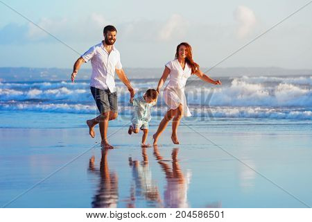 Happy family - father mother baby son have fun together child run with splashes by water pool along sunset sea surf on black sand beach. Travel lifestyle parents with kids on summer vacation.