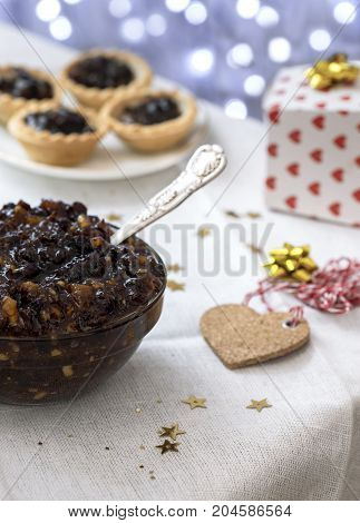 arrangement of homemade traditional Christmas mincemeat focus on the subject with mince pies and bokeh lights background de focused to ad copy space