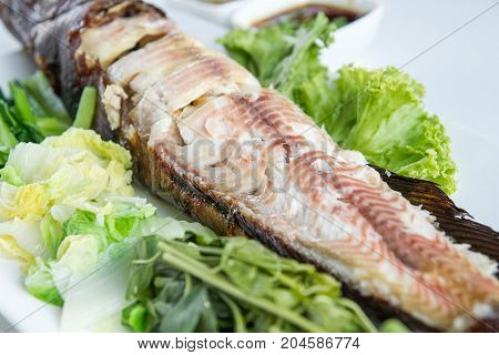 Salt-Crusted grilled fish serve with mixed vegetables on white dish