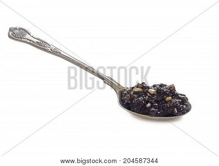 traditional english christmas mincemeat homemade with mixed fruits on a large silver spoon isolated on a white background