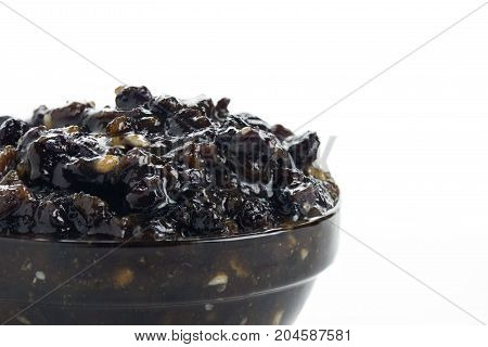 macro shot of homemade christmas traditional mincemeat in a glass bowl on a white isolated background