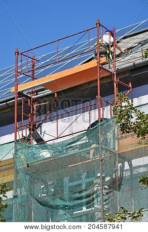 Roofers are working in height at the construction of a building