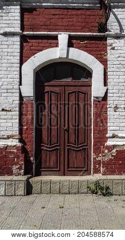 Old door in an old building. Ancient architecture. Red door. Brown door.  Door.