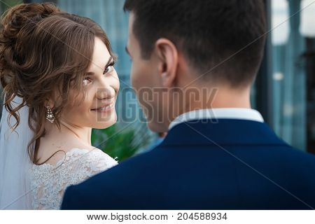 portrait of newlywed couple. Smiling bride in beautiful white wedding dress looking at the camera and asian groom in dark blue suit . back view