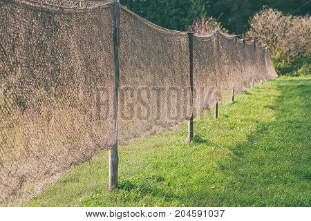 The fishing net is dried on wooden poles against a background of green grass on a summer sunny day