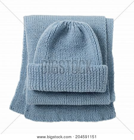 Knitted scarf and cap of blue color on isolated white background. Top view.