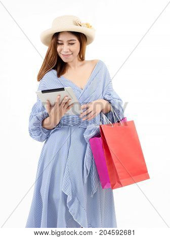 portrait of asian young woman holding shopping bags watching special offers in her tablet with screaming and wondering isolated on white background sale season online shopping concept soft focus