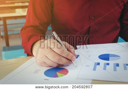 close up hand working finances about cost and writing with business strategy diagram report on desk at home office income and expenses money cost savings and economy concept