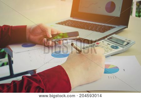 hand working and writing with smart phone calculate finances about cost with business strategy diagram report laptop computer on desk at home office income and expenses money cost savings concept