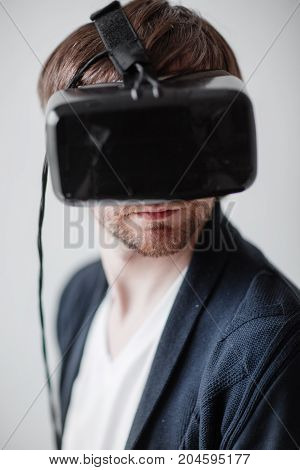 Handsome man wearing virtual reality glasses isolated on a gray background.