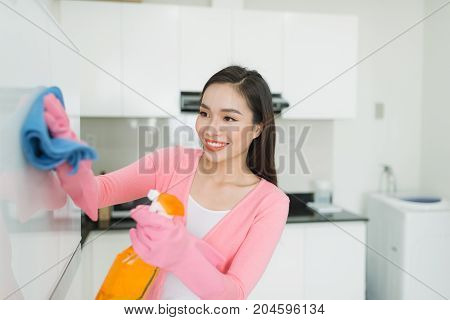Beautiful Asian Young Woman In Protective Gloves Cleaning Kitchen Cabinet