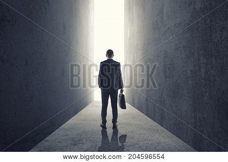 Silhouette of businessman entering giant doorway from dark room