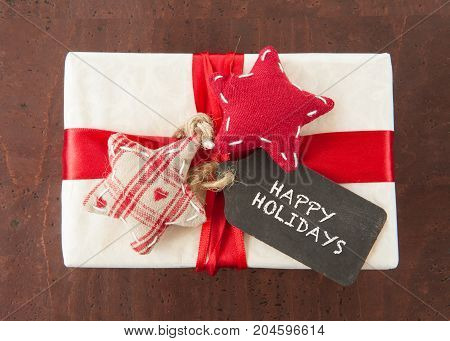 Little wrapped present with red ribbons and a gift tag for christmas