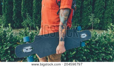 Unrecognizable tattoed young man standing with longboard in summer park.