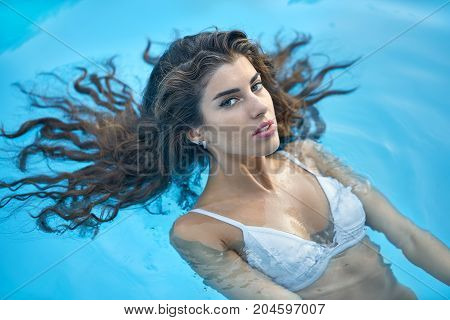 Gorgeous girl with parted lips in a white swimsuit lies on the back in the swimming pool outdoors. She looks into the camera. Closeup. Horizontal.