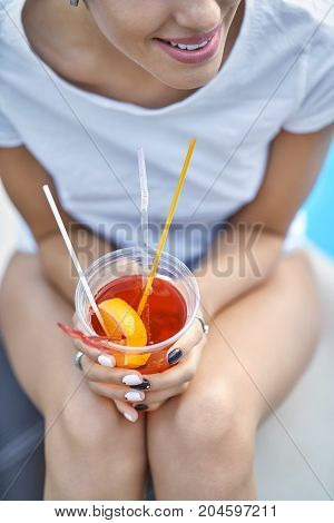 Young girl with a smile in a white T-shirt sits on the pool's edge outdoors. She holds an orange cocktail in the hands. Closeup low aperture photo. Vertical.