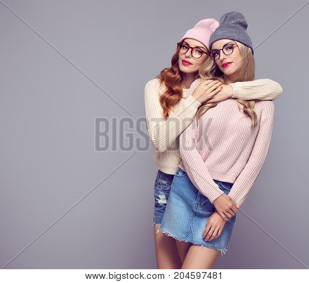 Fashion. Young woman Hugging in Stylish Autumn outfit. Pretty Sisters Best Friends Twins. Hipster Blond Redhead Model, fashion Cozy jumper, Glasses. Beautiful Girls in Trendy Beanie hat.Vanilla color