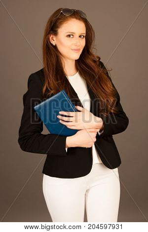 Attractive Business Woman With Notebook Over Gray Background