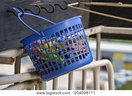 Closeup of blue plastic basket full of clothespins