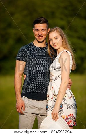 Active young couple on a wlak in the park on hot summer afternoon