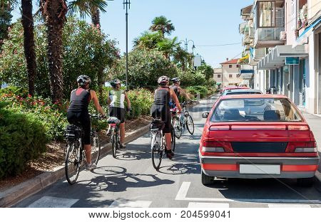 A group of cyclists rides around town on a Sunny day on the paved road. The horizontal frame.