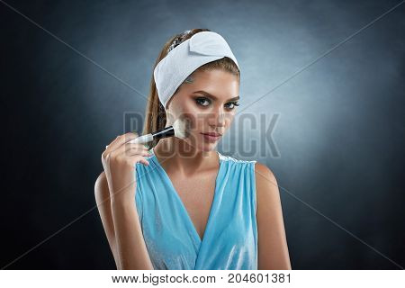 Studio portrait of pretty woman wearing in blue top and bandage, holding in hand ankle and drawing blush for herself. Beautiful brunette girl making makeup, looking at camera. Beauty concept.