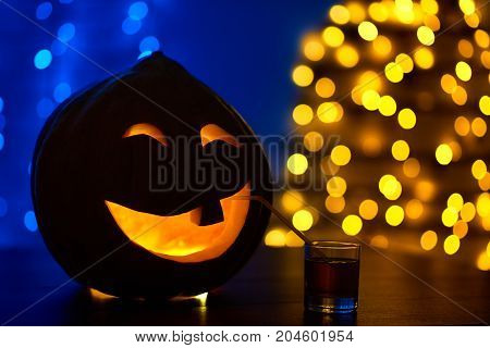 Scary and funny pumpkin with one tooth, big smile, decorated for Halloween party having fun, drinking juice or cocktail from glass on table. Dark background with ights. Autumn conceptual holiday.