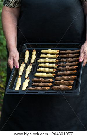 Female hands hold a baking tray with cookies Fingers