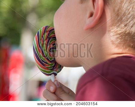 Close up of Eight Years Child Licking Colorful Round Lollipop