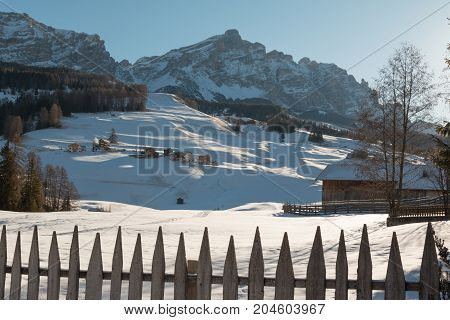 Wooden Fence Houses and Mountains with Snow in Europe: Dolomites Alps Peaks for Winter Sports