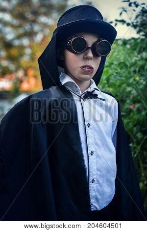 Elegant vampire with hat and black raincoat