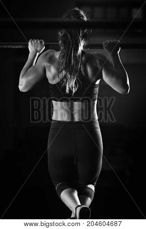 Woman Athlete Doing Pull Ups, Black And White Image, Black Background