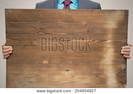 Smiling business man in suit and glasses holding in hands empty bill board with copy space close up. Advertisement board. Product presentation.